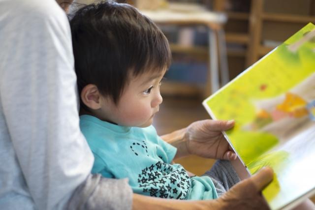 絵本を読んでもらう3歳児