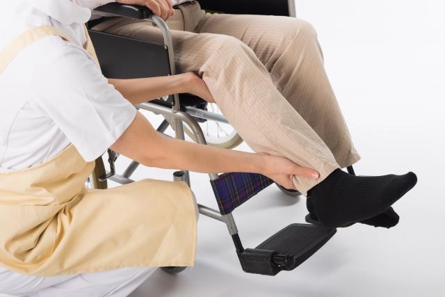 車椅子に乗って介護されている