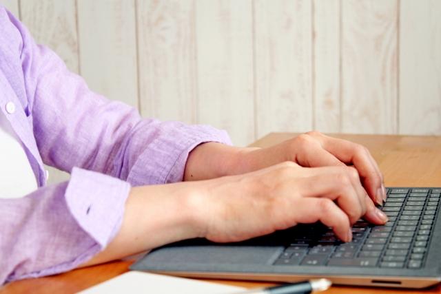 女性がキーボードを打つ